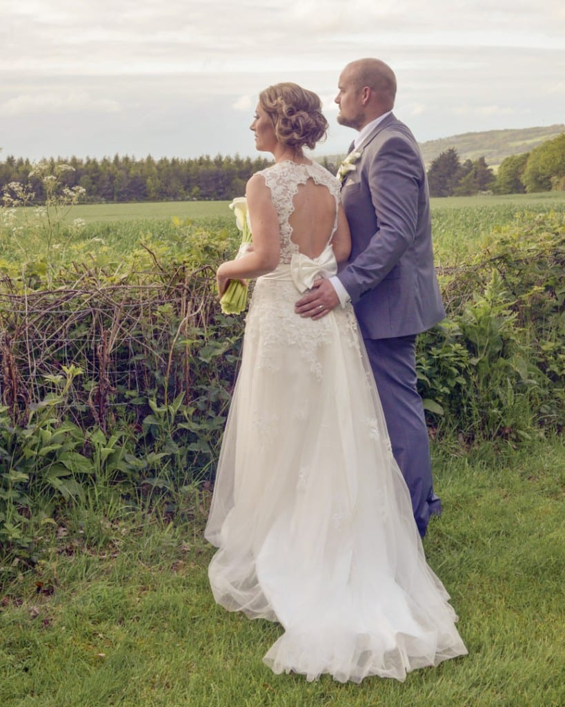 bride and groom looking out over fields